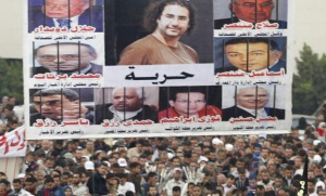 Protesters gather under a poster showing Abd El Fattah, a blogger arrested by the military, during a demonstration at Tahrir Square in Cairo