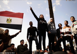 [On 25 January 2013, a protester leads chants amidst clashes with police, on the second anniversary of Egyptian revolution. Ultras Ahlawy (hardcore football fans) clashed that day with Central Security Forces guarding the Interior Ministry, in revenge for the killing of their colleagues in Port Said stadium last year, alleged to have been intentionally killed by police. Image originally posted to Flicker by Jonathan Rashad]