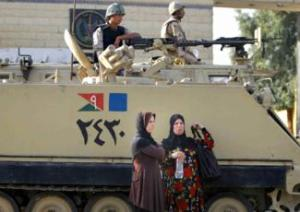 Two women wait near an armored army vehicle guarding Torah Prison, where ousted President Hosni Mubarak is held in Cairo, and expected to be released. Image by Amr Nabil via Associated Press.